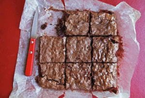 A slab of Katharine Hepburn brownies cut into 9 pieces, on parchment paper, with a knife nearby