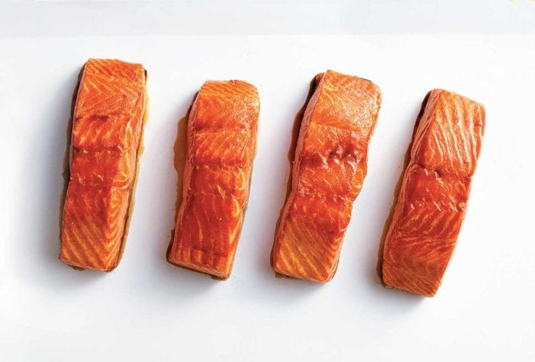 Four fillets of maple glazed salmon of a white square platter