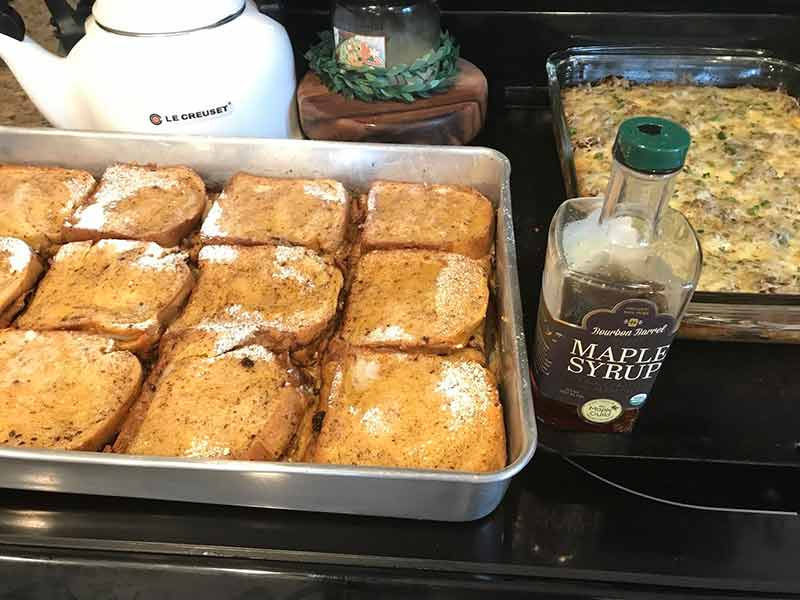 Pan filled with 12 pieces of brioche French toast, maple syrup, tea pot