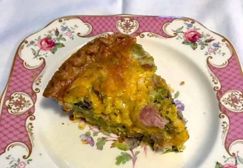 A slice of Broccoli-Cheddar quiche on a flowered plate