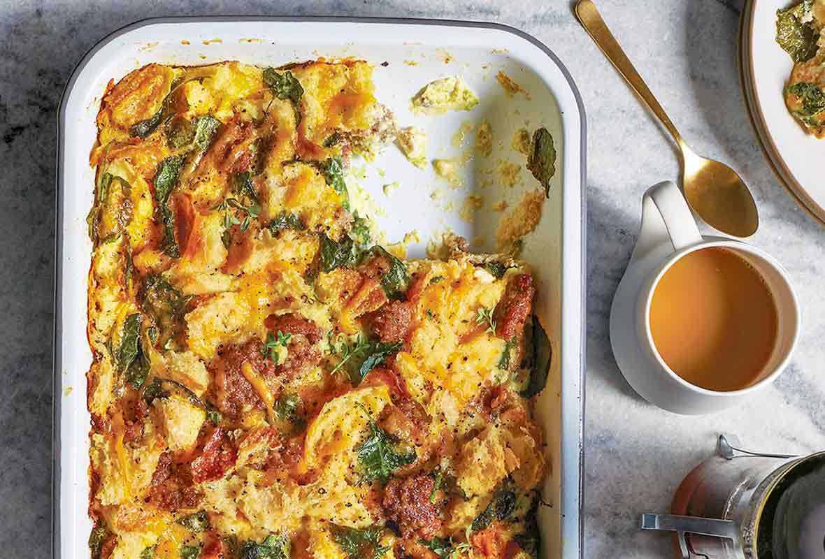 Baking dish of sausage egg breakfast casserole of bread, eggs, sausage, tomato, kale, and Cheddar cheese, a plate and tea nearby