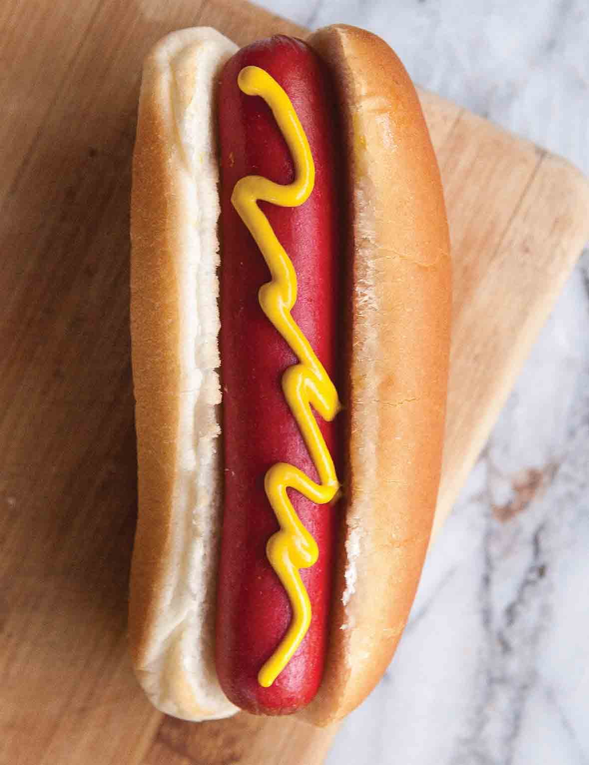 A hot dog in a white bun with a squiggle of mustard on a wooden board.