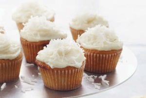 Cake stand with 7 frosted coconut cupcakes, four unfrosted cupcakes on the table, a bowl of frosting