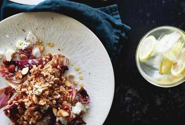 Two white plate of farro salad with radicchio and almonds, bowl of lemons, napkin