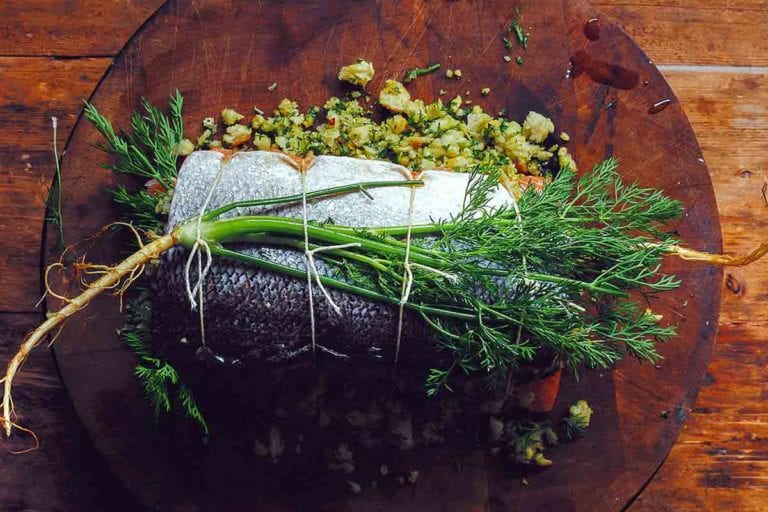 A whole herb stuffed baked salmon filled with bread crumbs and herbs and tied with kitchen twine.