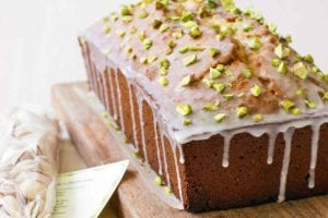 A pistachio lover's pound cake on a wooden cutting board with a mesh bag of pistachios beside it.