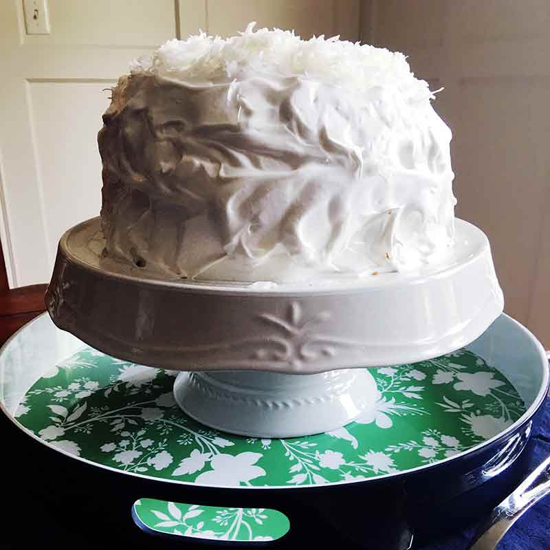 A Magnolia Bakery coconut cake--with meringue frosting and topped with coconut on a white cake stand, on a green tray