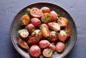 A grey bowl filled with roasted radishes, sprinkled with thyme.