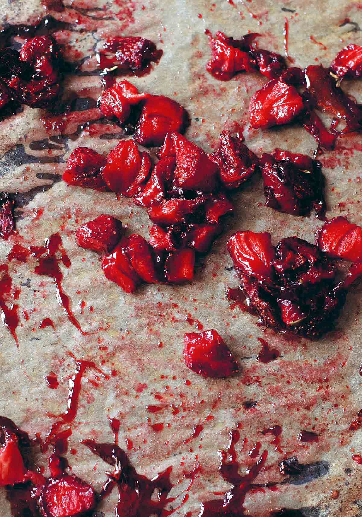 Chunks of roasted strawberries on a sheet of parchment.