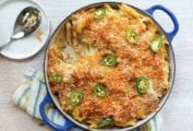 Blue casserole of spicy macaroni and cheese with breadcrumbs on top and sliced of jalapeno peppers