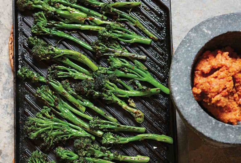 A cast-iron griddle filled with cooked broccolini and a bowl of red paste on the side.