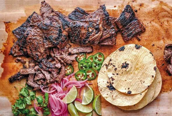 Cutting board with grilled skirt steak tacos, sliced jalepenos, tortillas, lime wedges, pickled onions, cilantro