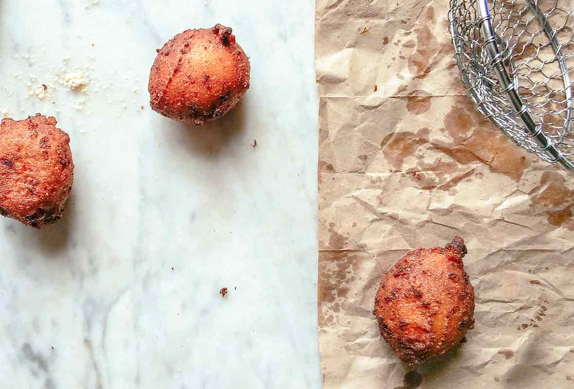 Three freshly fried hush puppies on a marble top and brown paper bag, a spider strainer bear by