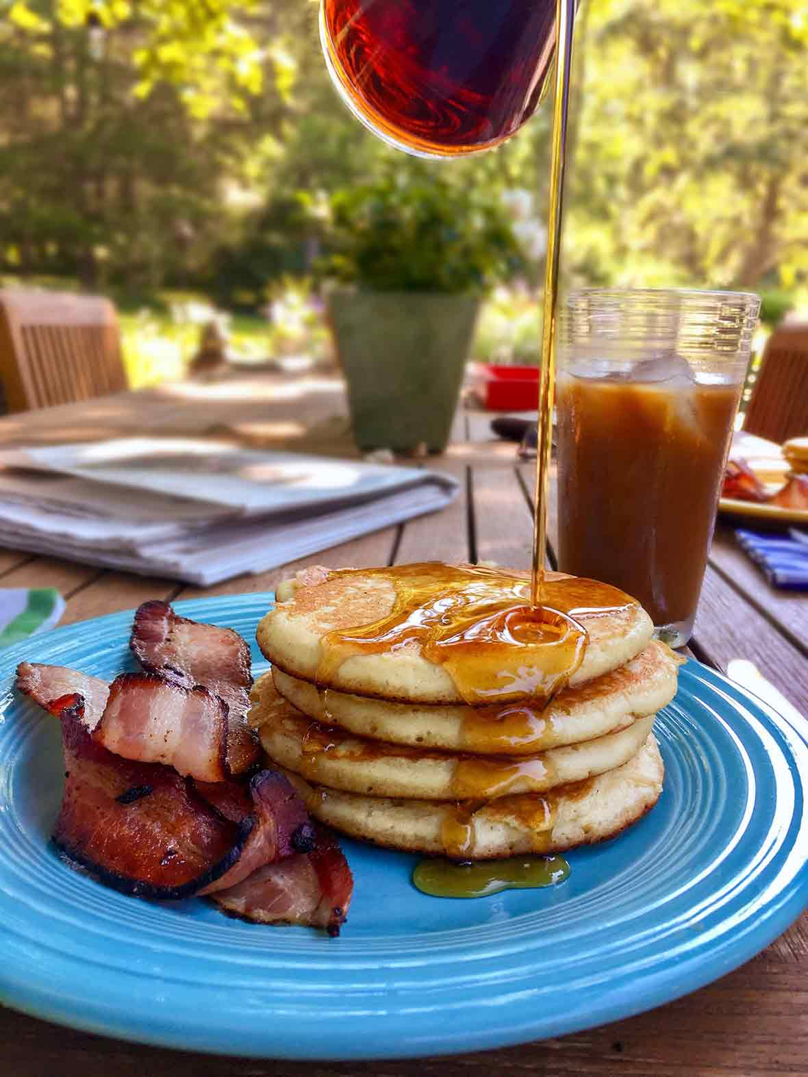 A blue plate topped with three light and fluffy pancakes, maple syrup, and cooked bacon.