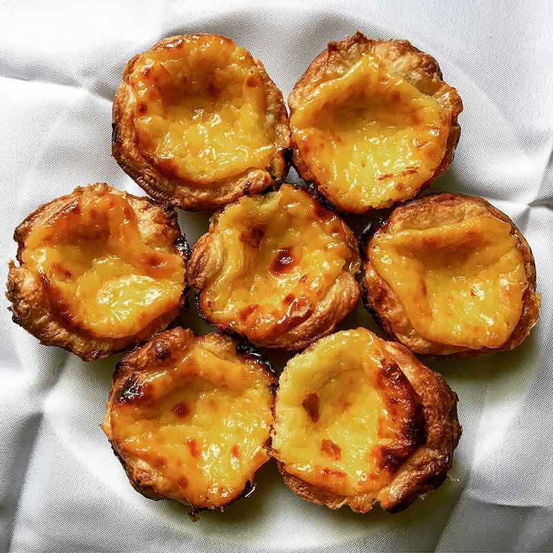 Seven pastéis de nata--Portuguese custard pastries with flakey shells filled with a mottled burnt surface