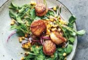 Plate of butter-basted seared scallops on a salad of watercress and sweet corn