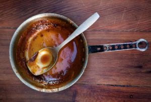 An empty pot and spoon with just a little spicy bourbon barbecue sauce at the bottom on wood