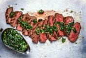 A sliced steak chimichurri with a gravy boat filled with chimichurri on the side.