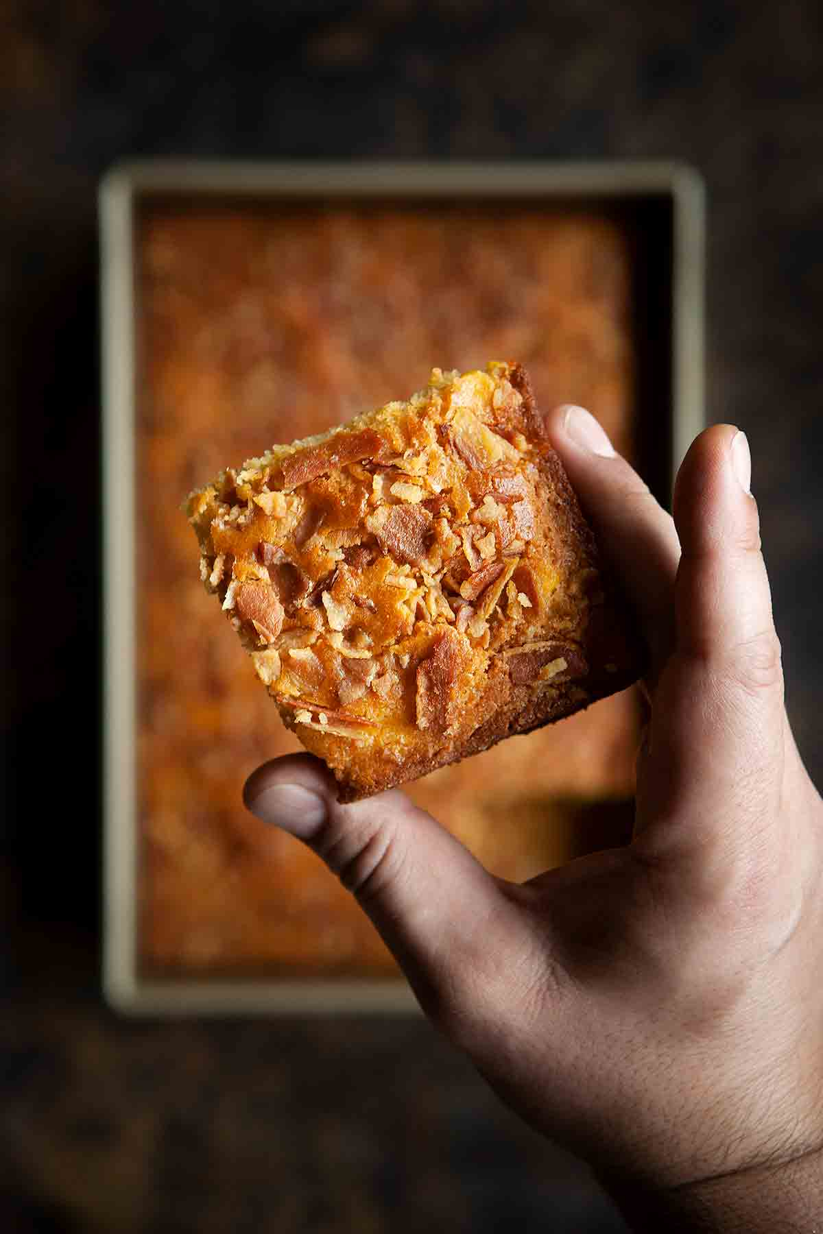 A man's hand holding a square of bacon cornbread