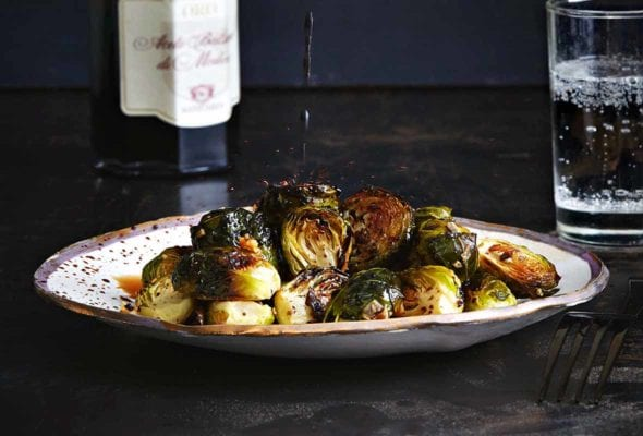A plate of roasted Brussels sprouts with a drizzle of balsamic vinegar splashing down on it