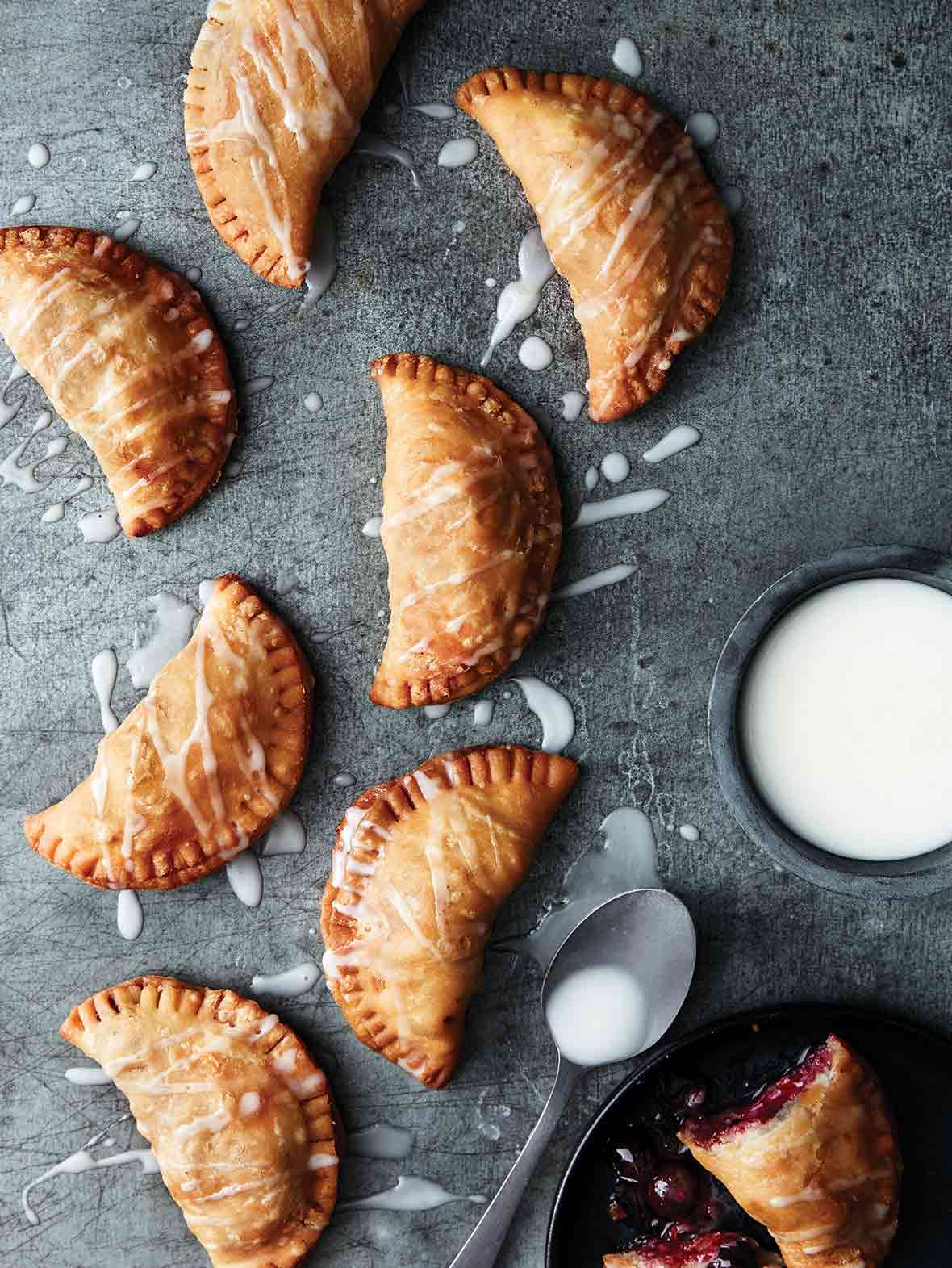 8 crescent-shape blueberry fried pies with Meyer lemon drizzle sauce nearby all on a piece of slate