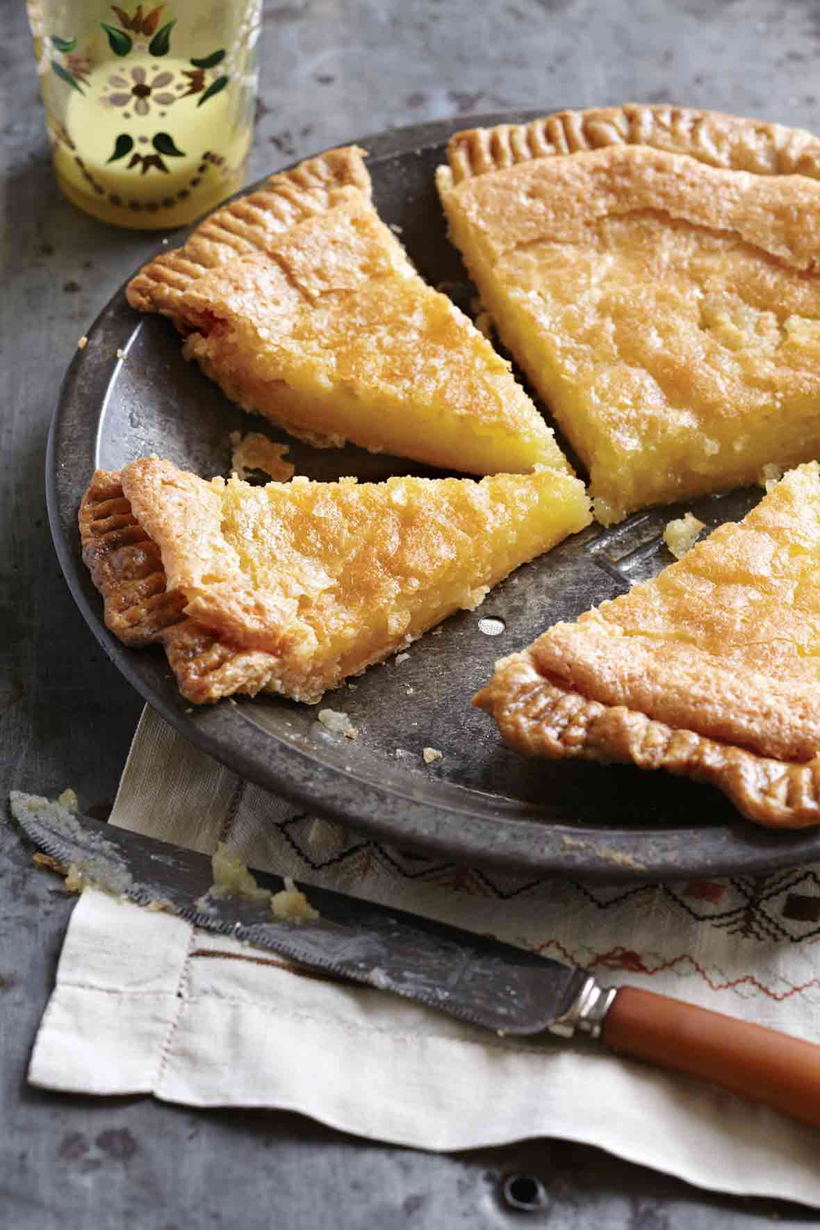 A chess pie with a homemade crust cut into four slices in an antique tin pie plate on top of a napkin
