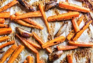 Baking sheet lined with parchment and covered with easy roasted carrots and onions with burnt edges