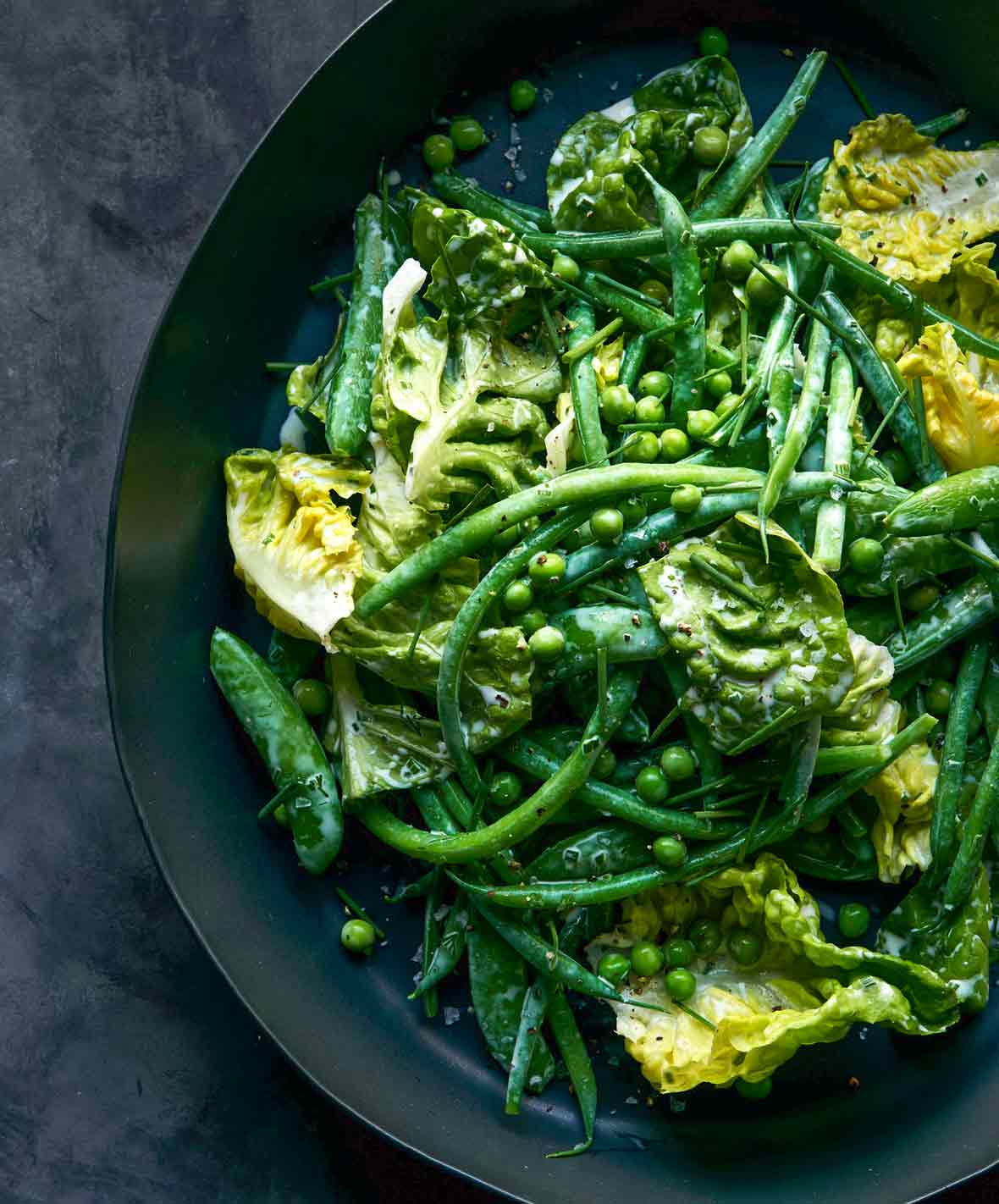 A black bowl fill with green beans, peas, and lettuce tossed with buttermilk ranch dressing