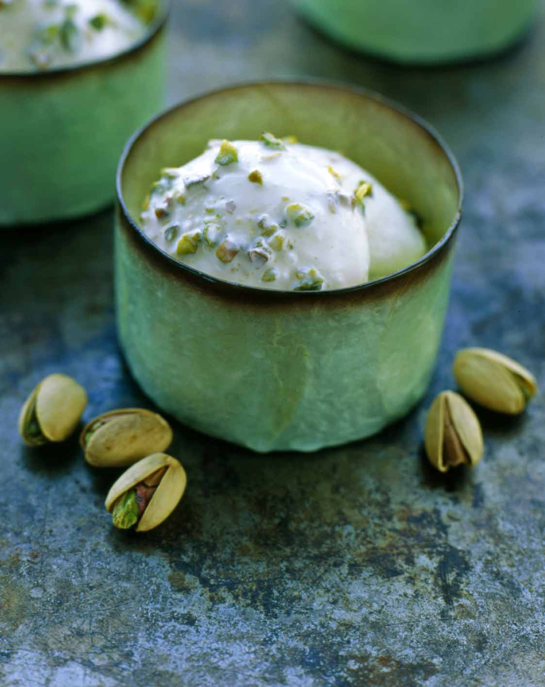 A few green cups filled with pistachio gelato with five pistachios beside