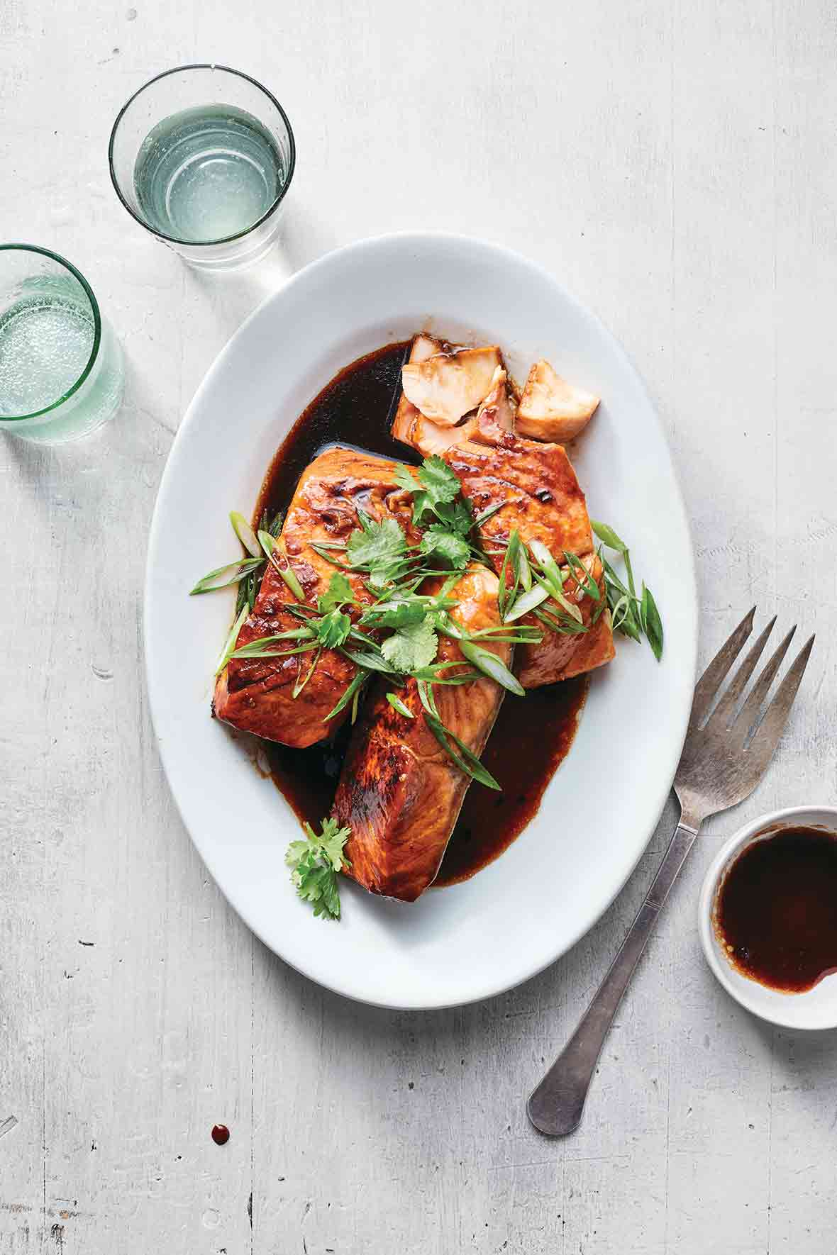 Pressure cooker vietnamese caramel salmon, sliced green onion, and soy sauce on a white plate