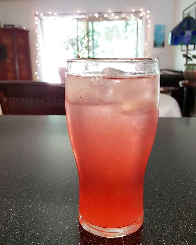 A tall glass of pink rhubarb vodka