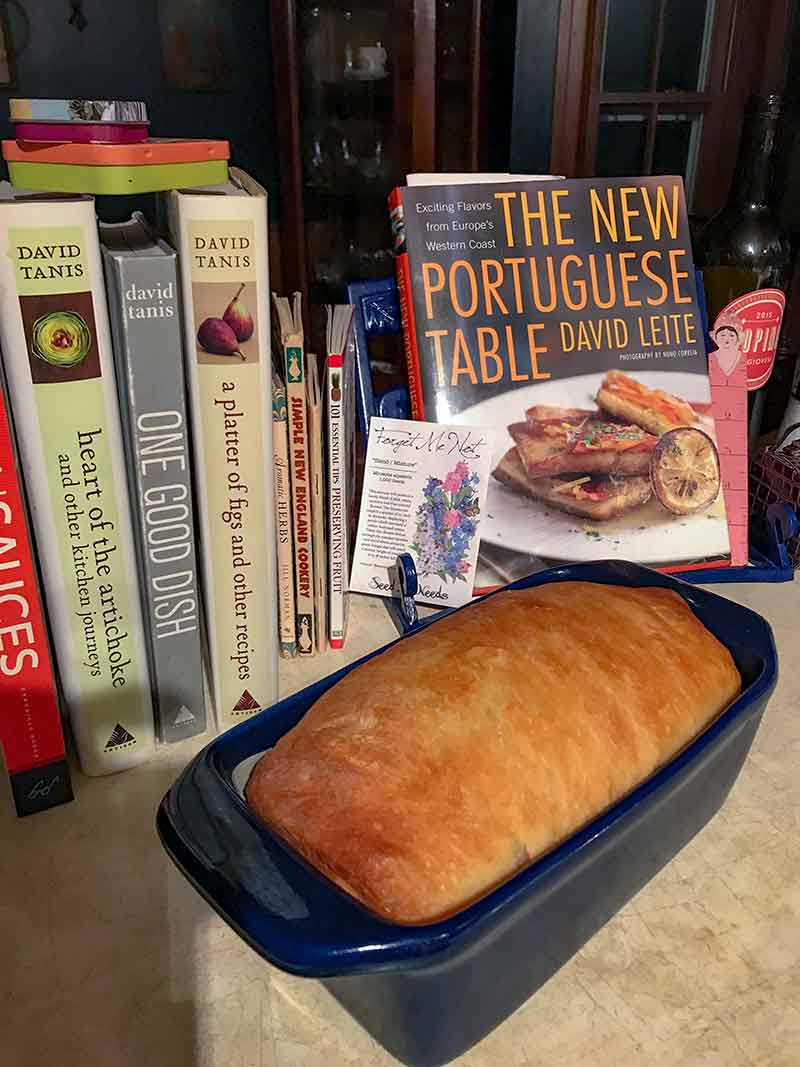 a loaf of homemade sandwich bread in a pan in front of cookbooks