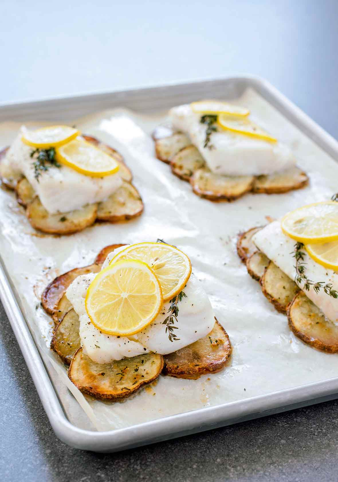 A parchment-lined baking sheet with four roasted cod fillet on top of roasted potatoes slices and topped with lemon slices