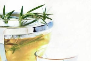 A pot of rosemary infused tea with rosemary sprigs sticking out the top and a glass beside it.