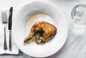 A white plate with a tarragon chicken leg and thigh on it, sliced onion and tarragon on top
