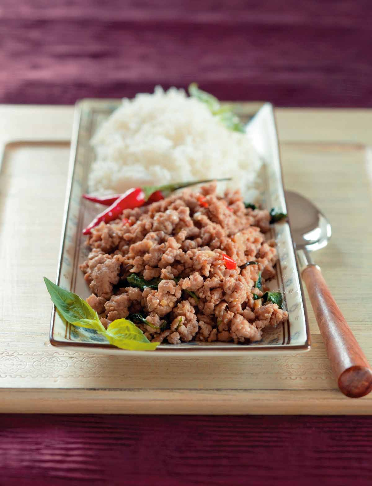 A rectangular serving dish filled with Thai basil pork, red chiles, and white rice with a serving spoon beside the dish.