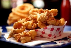 A red and white paper container of whole-belly fried clams, behind is onion rings and condiments