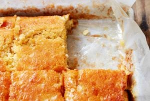 A parchment-lined square pan of buttermilk cornbread cut into squares, with one square missing.