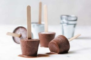 Chocolate fudge pops with popsicle sticks melting on a white surface.