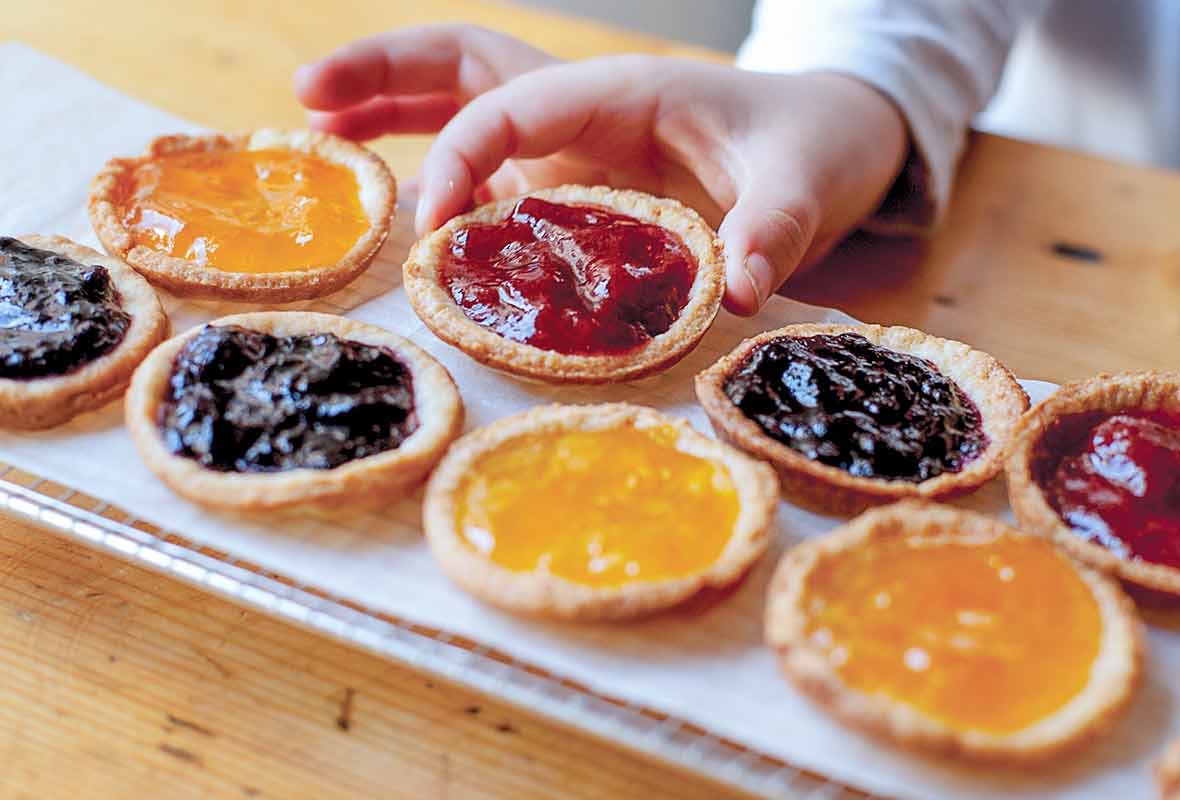 A tray of mini jam tarts--orange, strawberry, blueberry--one being picked up by a child's hand