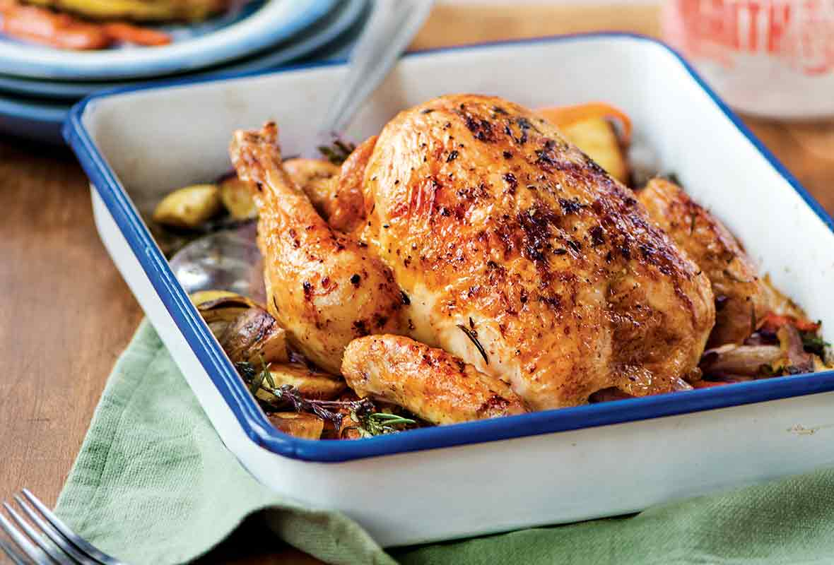 French roast chicken, called poulet rôti in French, in a white pan sitting top of roasted root vegetables