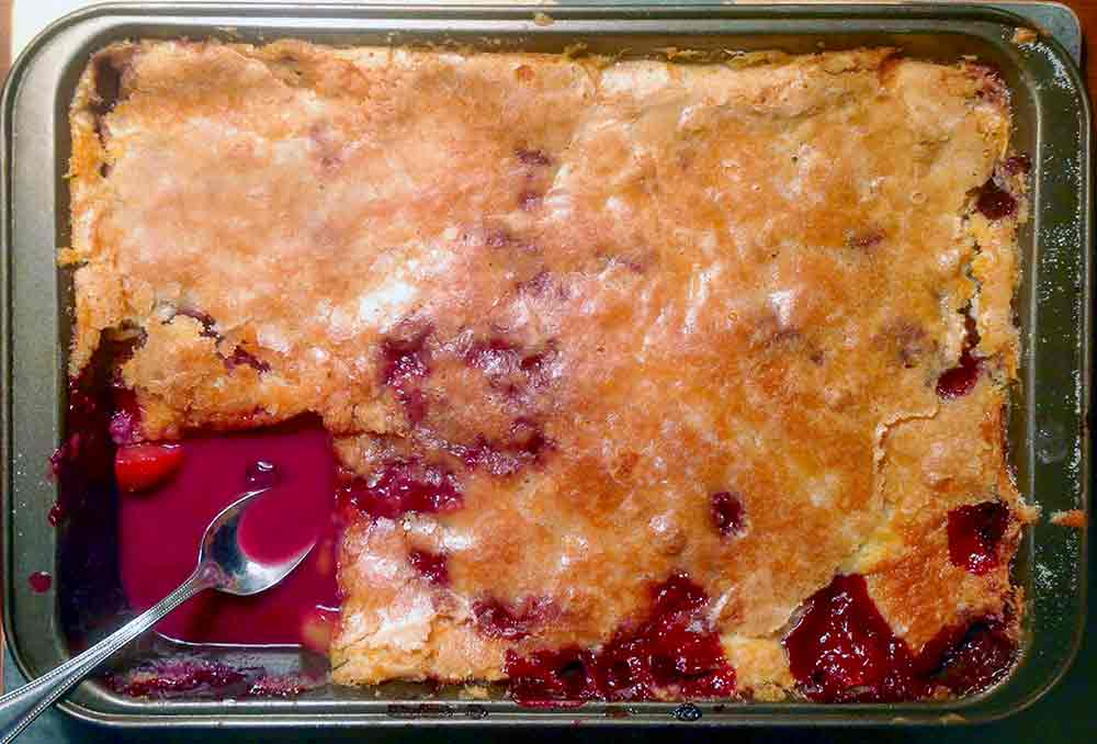 A rectangular baking dish with a peach cobbler, with one corner scooped out