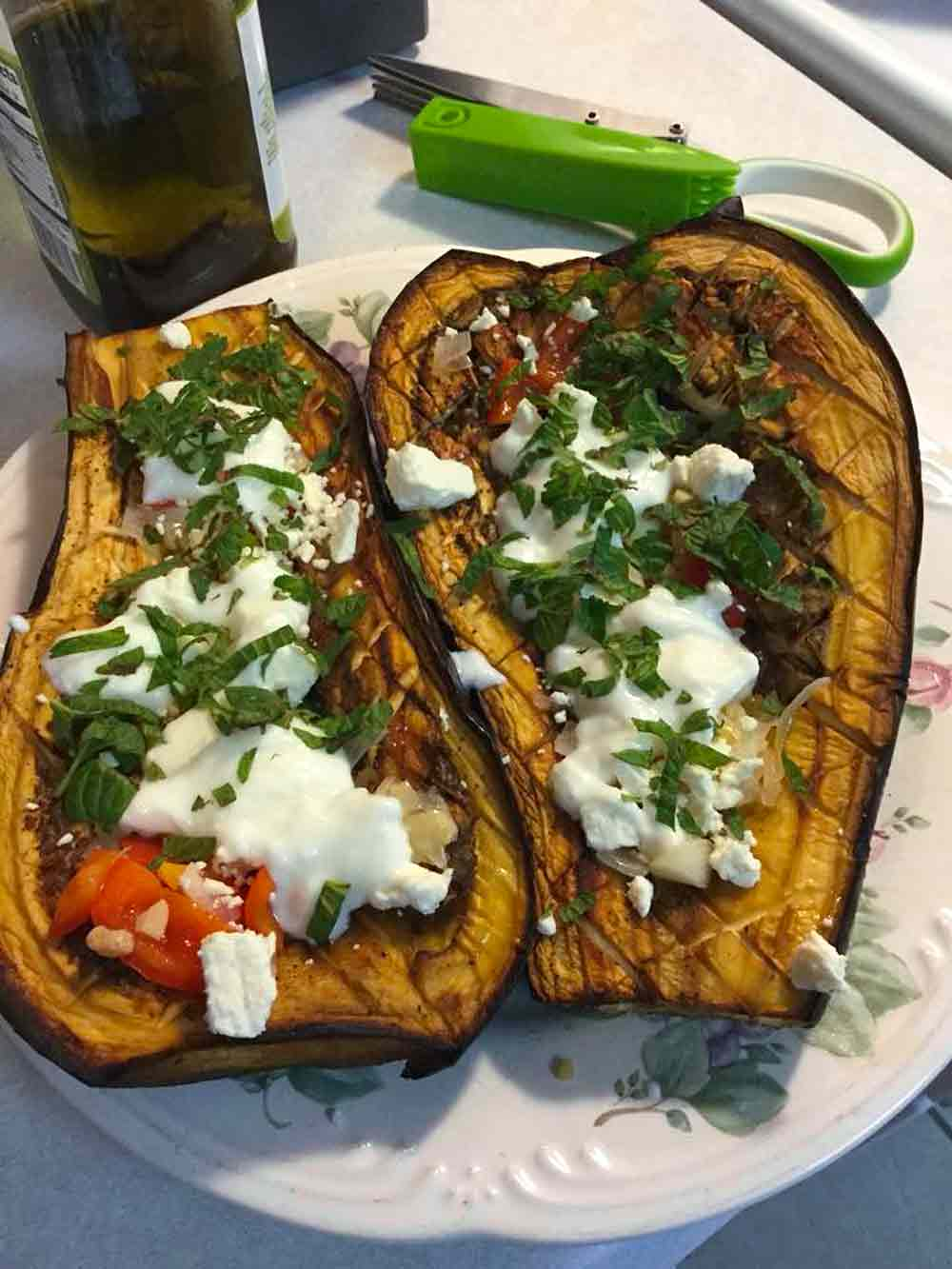 White and blue plate with Turkish baked eggplant topped with with chile, feta, and Mint