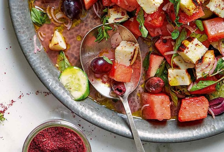 Bowl of watermelon, halloumi and za'atar salad, which also has cucumbers, olives, and grapes