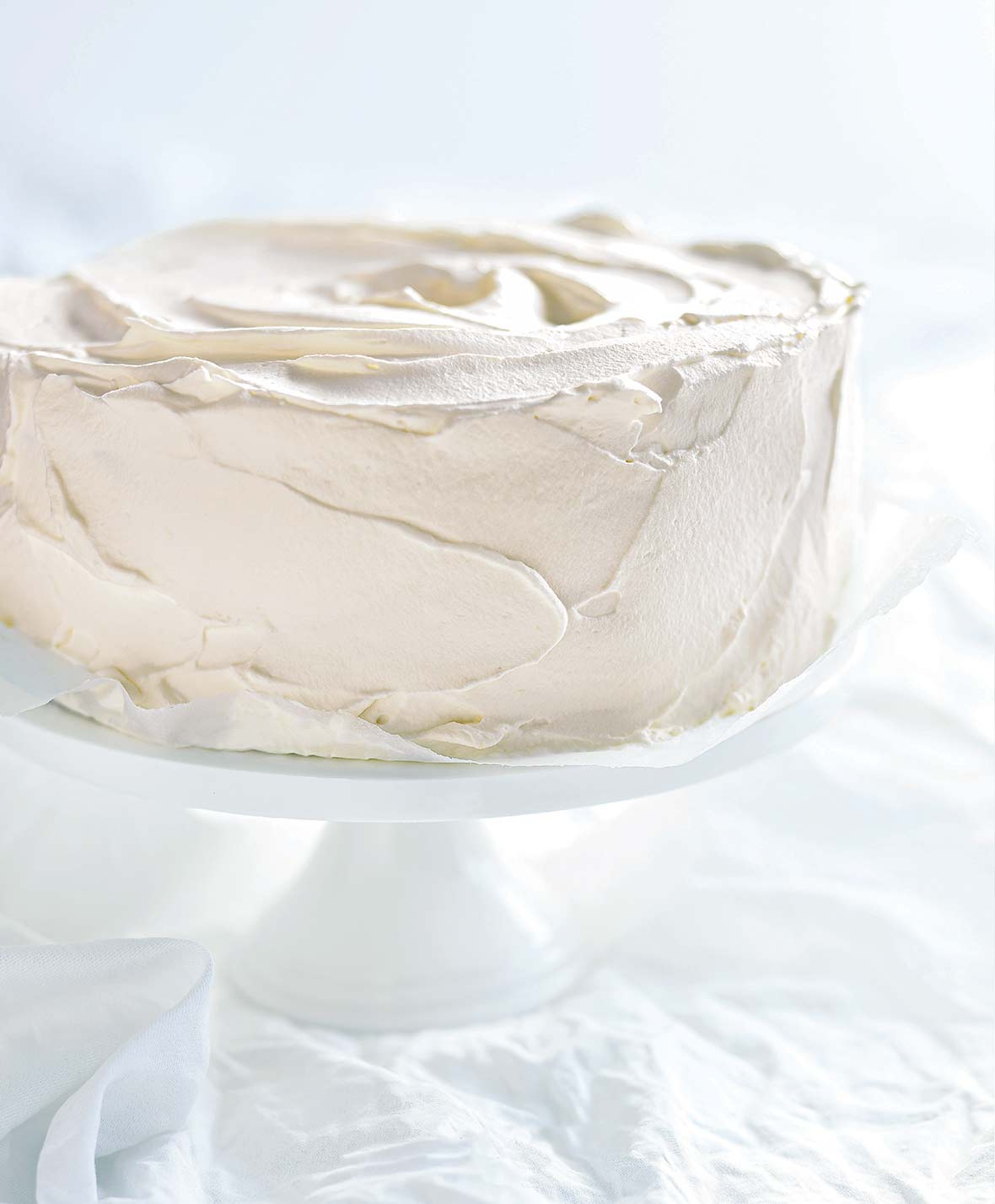 An angel food cake slathered in white chocolate frosting on a white cake stand on a white background