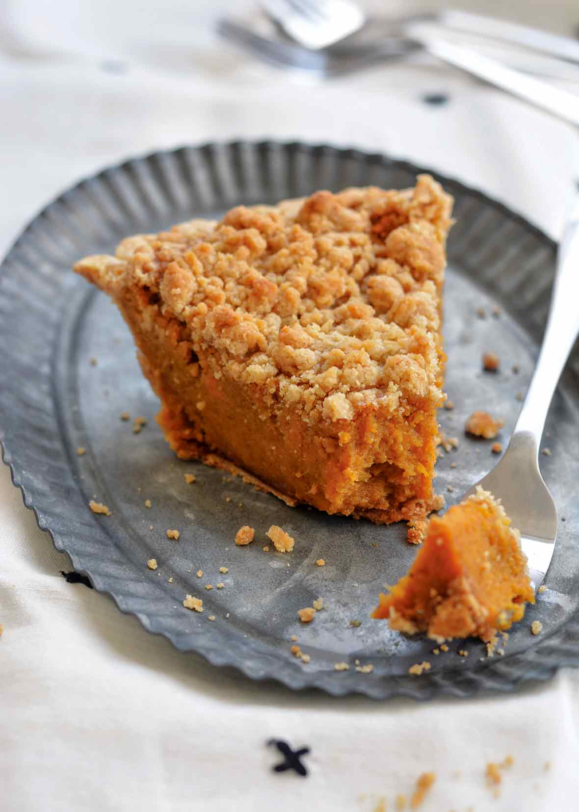 A wedge of bourbon sweet potato pie topped with a crumbly brown sugar streusel omn a metal plate