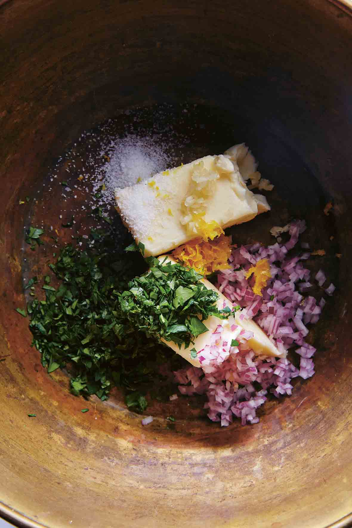 A clay bowl filled with butter, parsley, red onion, lemon zest, orange zest, and salt