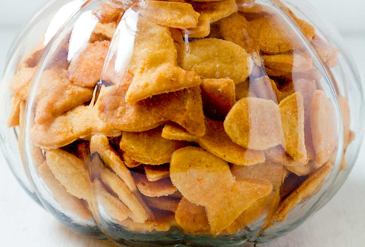 A glass jar filled to the brim with cheesy fish crackers.
