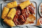 A tray of chicken thighs in a balsamic barbecue sauce, corn on the cob, glasses of beer, forks, and plates