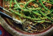 An Indian-style platter with pan-fried green beans and almonds topped with ground coriander, nearby a serving fork and spoon